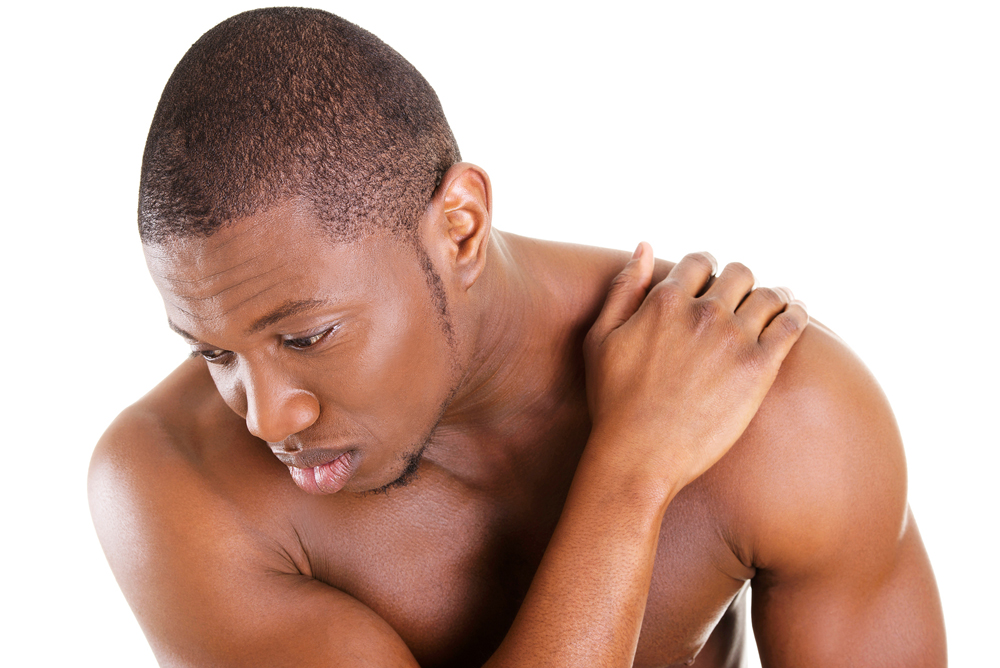 man holding his shoulder because he is suffering from pain